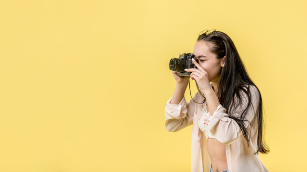 Long haired woman holding photo camera and taking picture Free Photo
