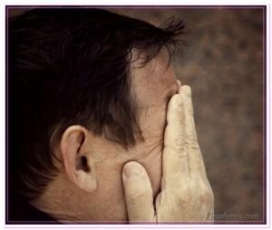 мужчина закрыл лицо руками