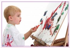 Маленький мальчик увлеченно рисует фото