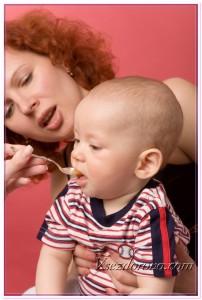 Молодя женщина кормит ребенка детским питанием