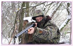 Охотник с ружьем в маскировочной одежде фото