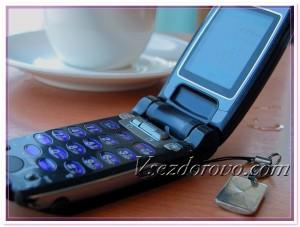 Мобильный телефон и чашка кофе на столе в кафе