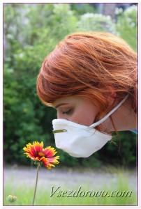 Девушка в маске нюхает цветок фото