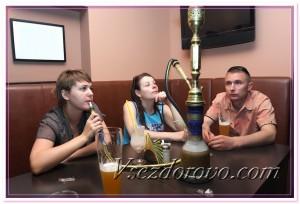 Молодые люди в кафе курят кальян фото