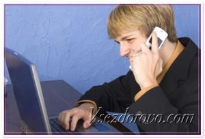 Мужчина с ноутбуком и телефоном фото