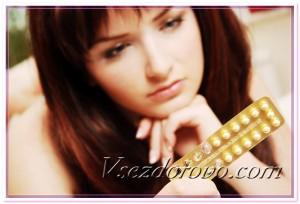 Молодая девушка смотрит на оральные контрацептивы