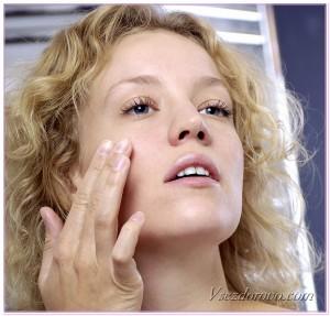 красивая девушка наносит крем вокруг глаз