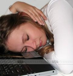 Девушка спит возле компьютера